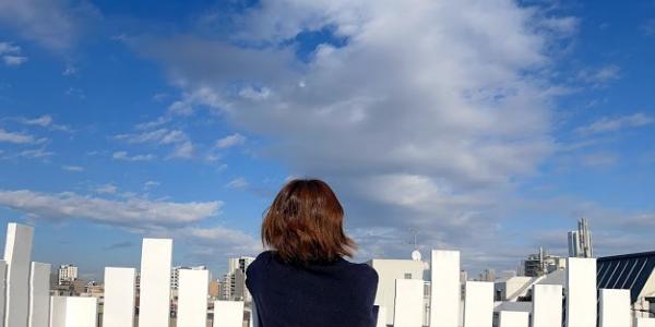 屋上で青空を見上げている女性