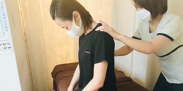 整体の施術の前に身体のアライメントをチェックしている女性