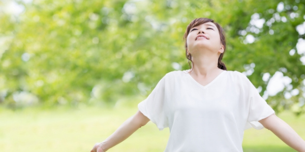 自然の中で深呼吸をしている女性