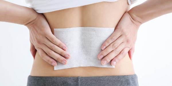 腰痛で腰にシップを貼っている女性