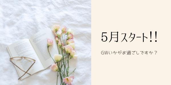 本と花と眼鏡を置いている白いシーツ