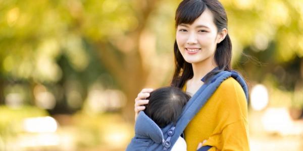 自然の中で子供を抱っこしているママ